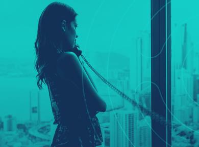 Mulher em frente a uma janela falando ao telefone com fio
